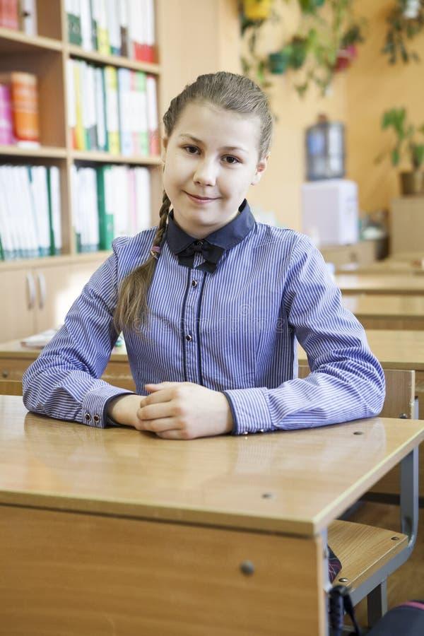 Retrato da menina preteen, estudante da escola primária que olha a câmera ao sentar-se na mesa de madeira fotografia de stock