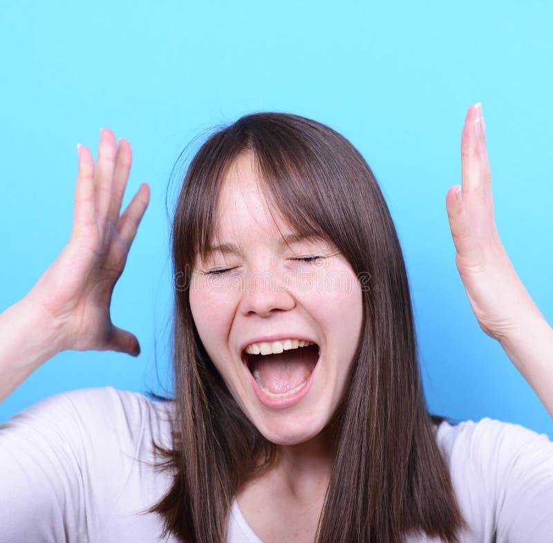 Retrato da menina que grita contra o fundo azul imagem de stock royalty free