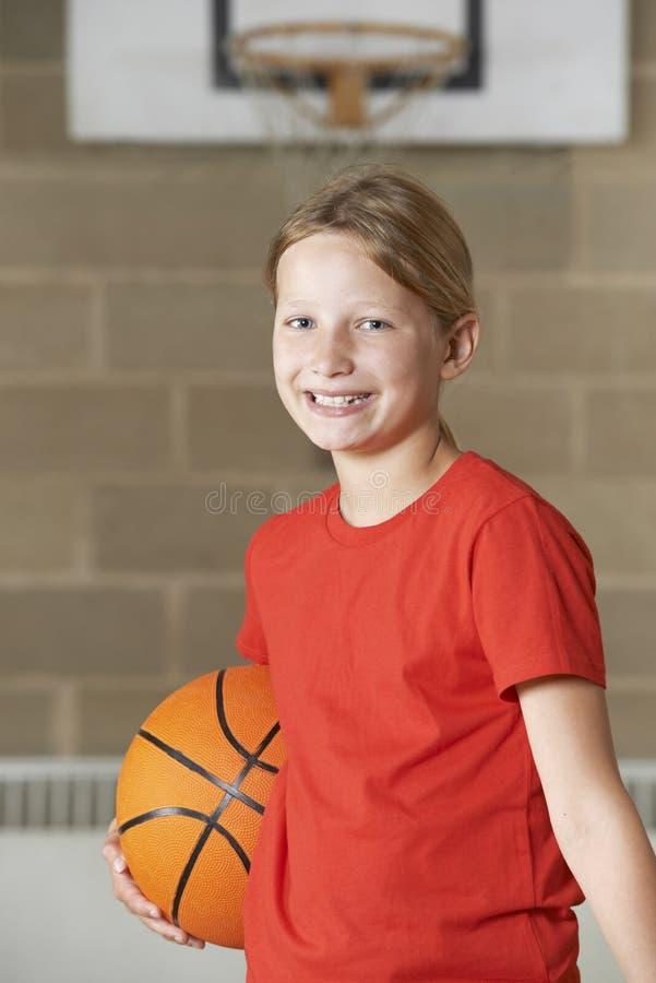 Retrato da menina que guarda o basquetebol no Gym da escola fotografia de stock