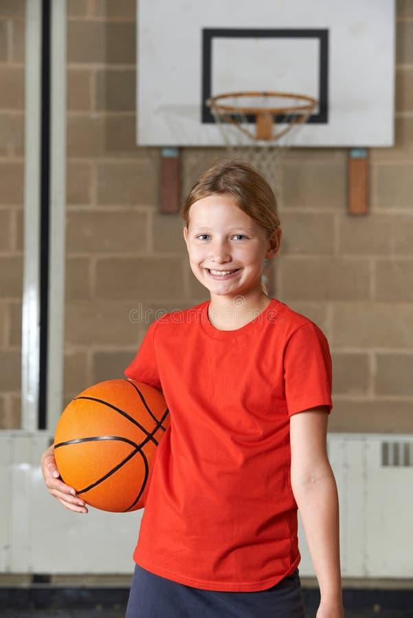 Retrato da menina que guarda o basquetebol no Gym da escola imagens de stock