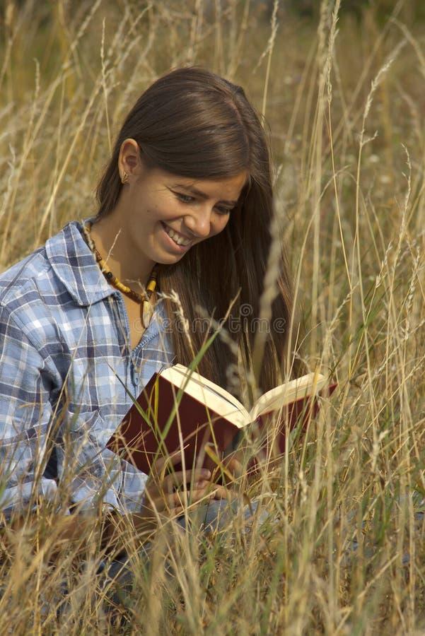 Retrato da menina que lê um livro na grama fotografia de stock royalty free