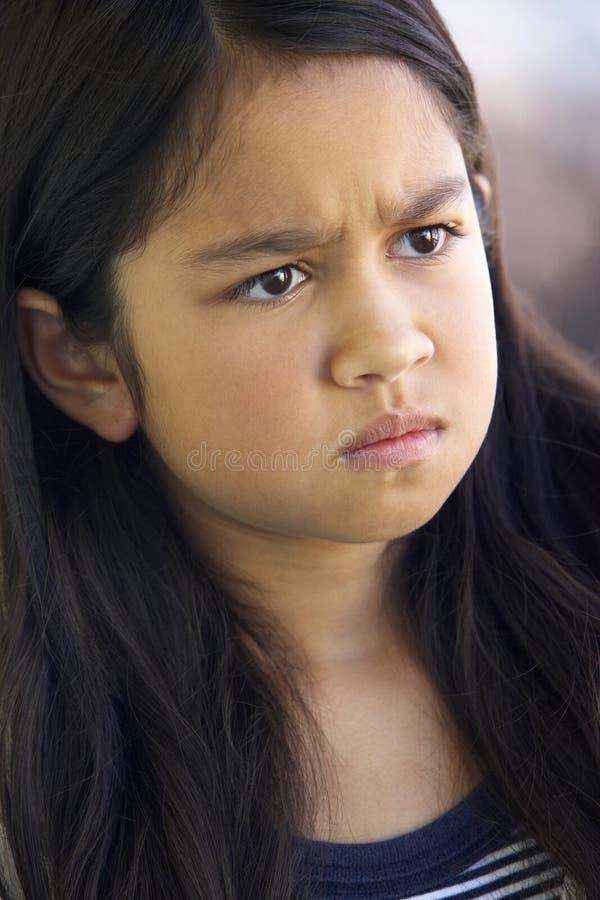 Retrato da menina que olha de sobrancelhas franzidas fotografia de stock
