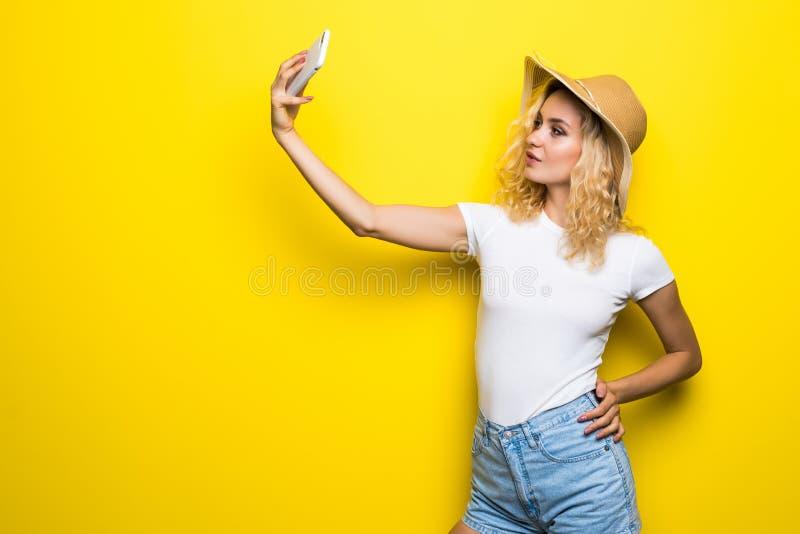 Retrato da menina que tem a vídeo-chamada com o amante que guarda o telefone esperto à disposição que dispara no selfie na câmera foto de stock royalty free