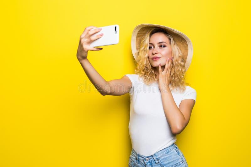 Retrato da menina que tem a vídeo-chamada com o amante que guarda o telefone esperto à disposição que dispara no selfie na câmera fotos de stock