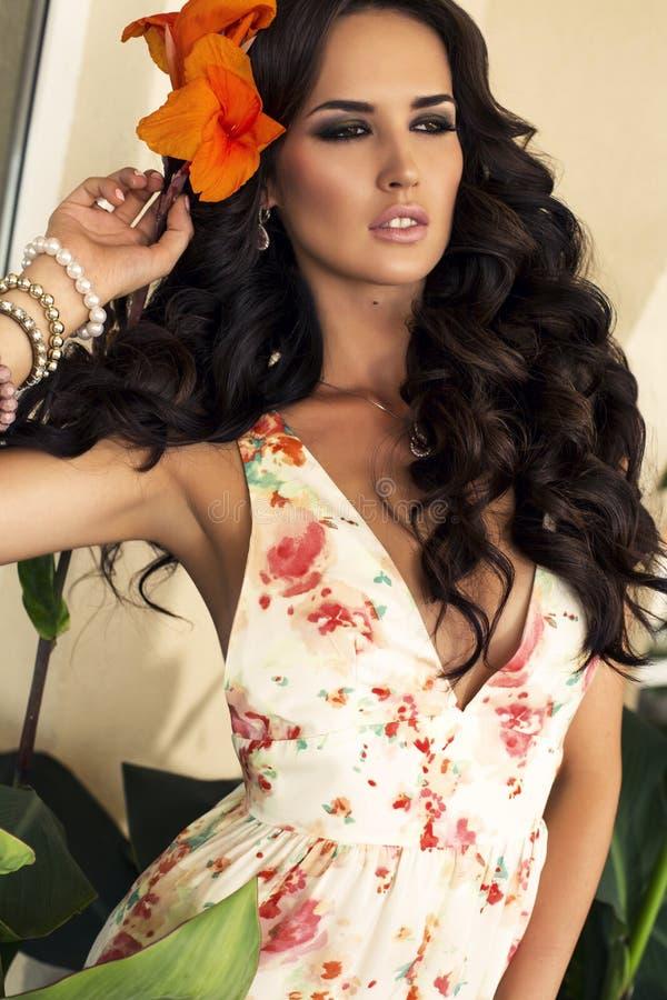 Retrato da menina 'sexy' com a flor em seu cabelo escuro longo foto de stock