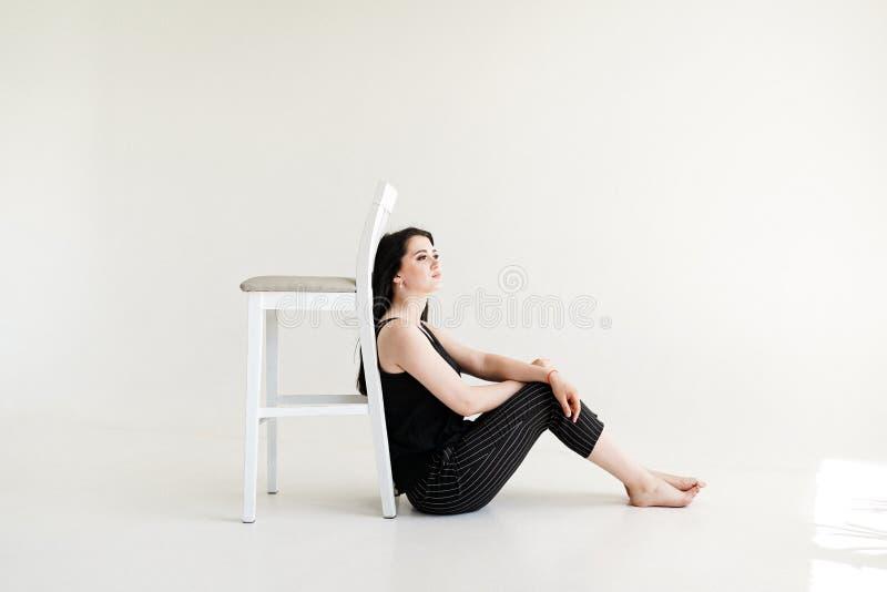 Retrato da menina smilling que senta-se com cadeira, em um fundo branco imagens de stock