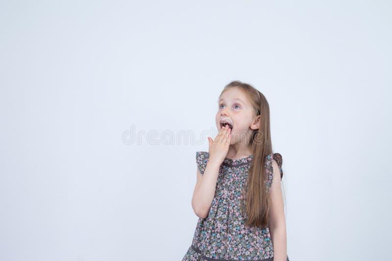 Retrato da menina surpreendida surpreendida adorável isolada em um branco Criança da menina que mantém as mãos na boca surpreendi imagem de stock