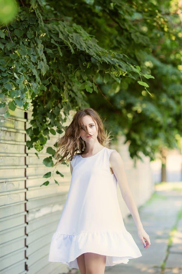 Retrato da menina urbana bonita no vestido branco curto na rua imagens de stock