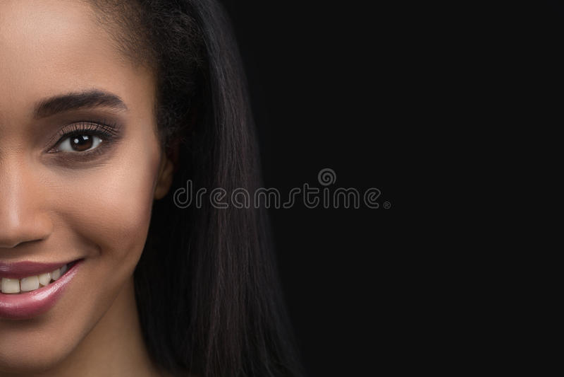 retrato da Metade-cara da mulher afro-americana sensível de sorriso bonita no fundo escuro fotografia de stock royalty free