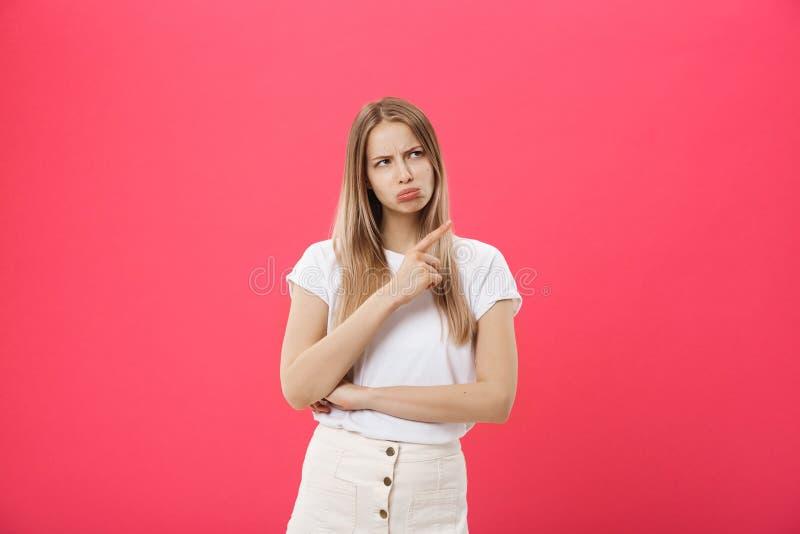 Retrato da moça atrativa com expressão triste e desapontado, apontando os indicadores em ambos os lados, isolados fotografia de stock royalty free