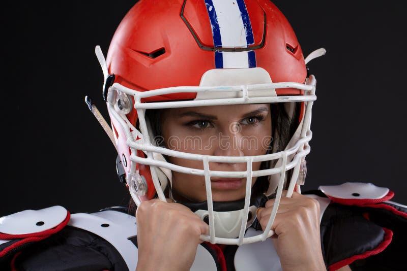 Retrato da moça atrativa 'sexy' com uma composição brilhante em um equipamento dos esportes para o futebol americano foto de stock royalty free