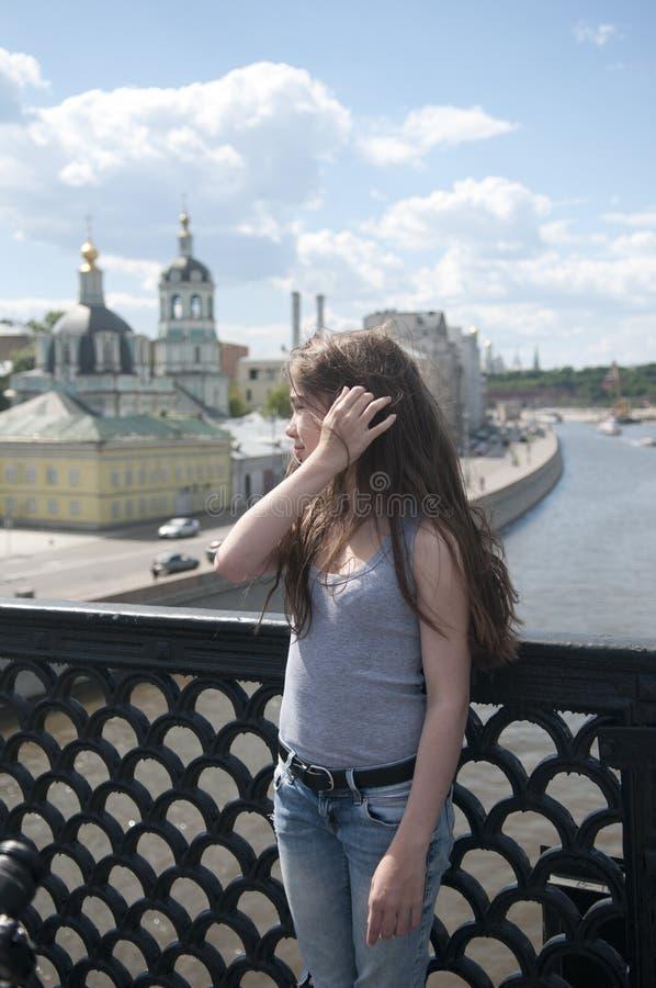 Retrato da moça bonita no fundo do céu azul da ponte com cabelo de sopro no vento imagens de stock