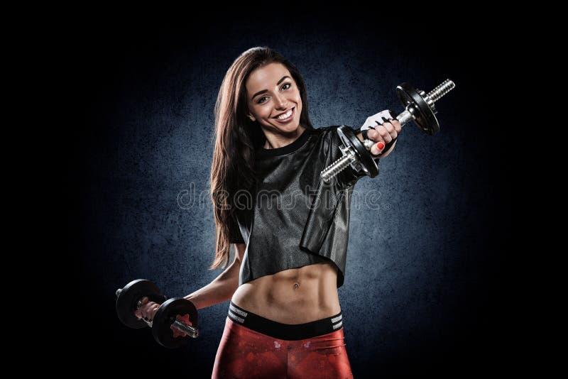 Retrato da moça bonita que exercita com pesos imagem de stock