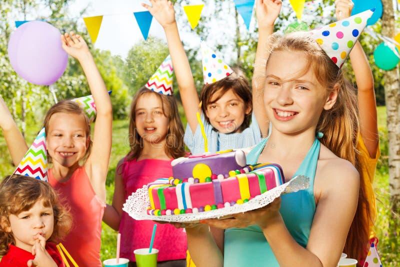 Retrato da moça de sorriso que guarda o bolo de B-dia imagem de stock
