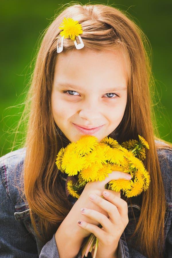 Retrato da moça de sorriso que guarda o ramalhete das flores em han fotografia de stock royalty free