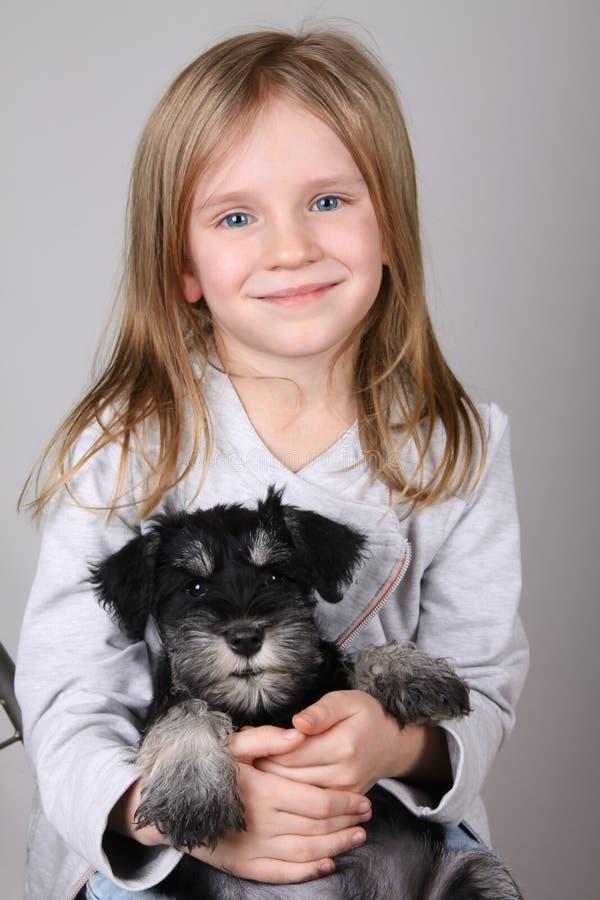 Retrato da moça loura adorável que sorri guardando o cachorrinho do Schnauzer imagem de stock