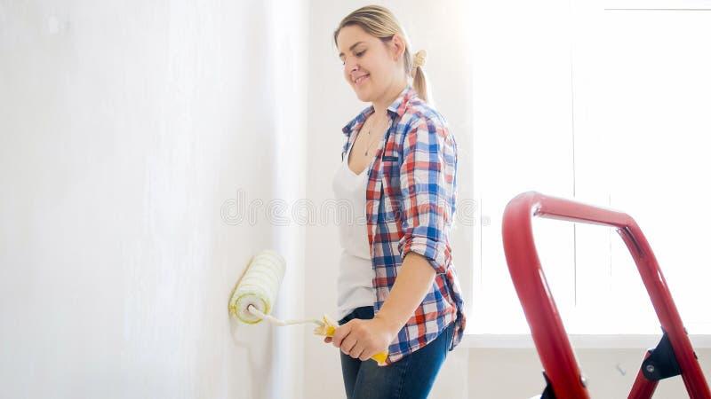 Retrato da moça na camisa quadriculado com pintura do rolo na casa nova imagem de stock