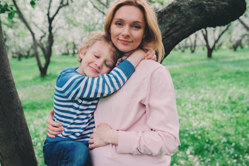 Retrato da mola da mãe grávida feliz que aprecia o dia morno com filho da criança imagem de stock royalty free