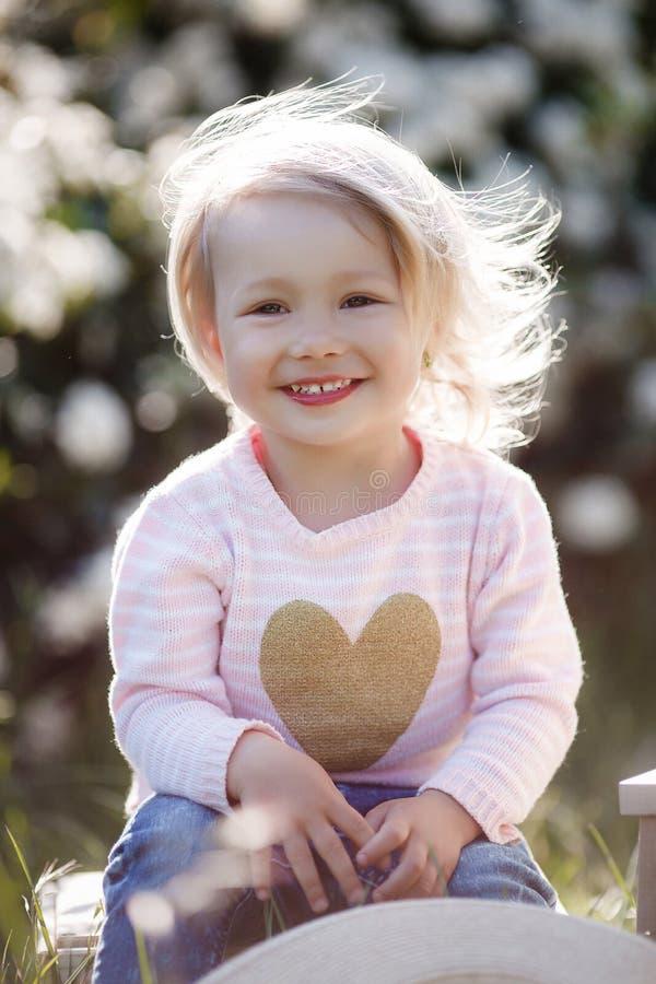 Retrato da mola de uma menina encantador que anda em um parque florescido imagem de stock