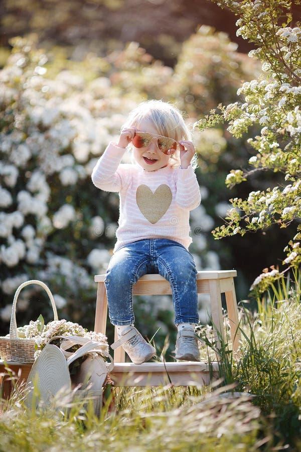 Retrato da mola de uma menina encantador que anda em um parque florescido fotografia de stock