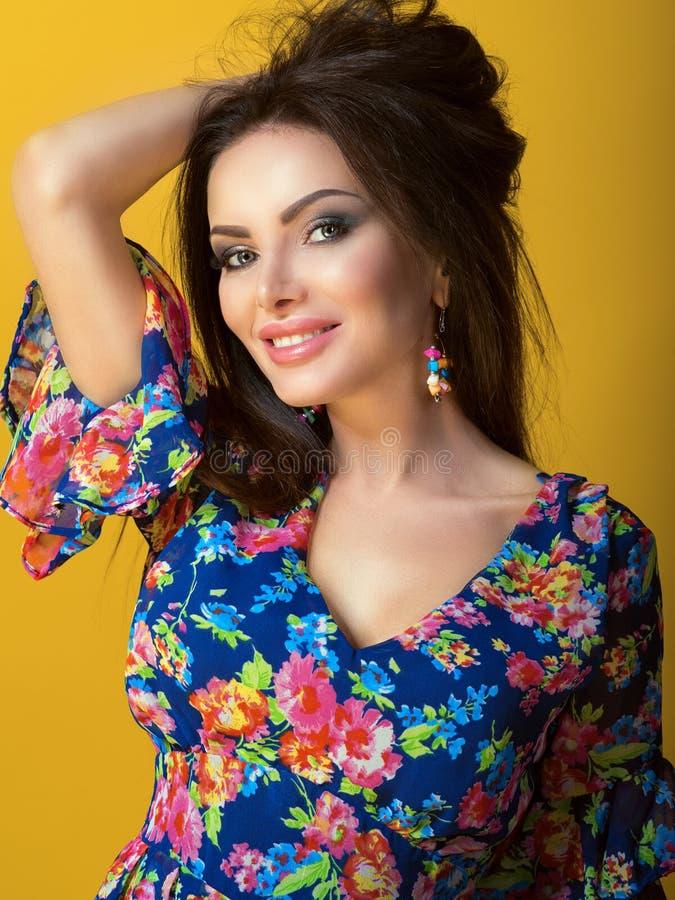 Retrato da morena de sorriso bonita nova no vestido decotado azul com a cópia floral brilhante que guarda a mão acima em seu cabe fotografia de stock