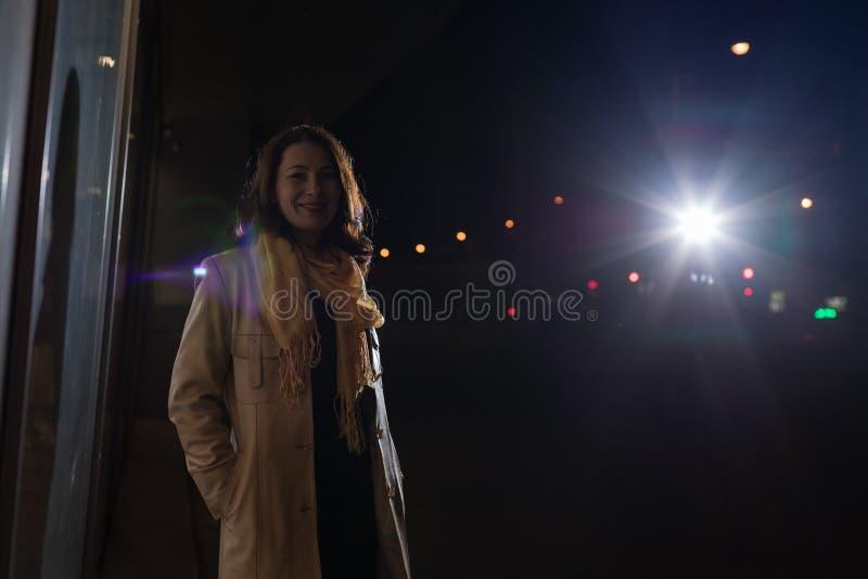 Retrato da morena da menina na rua e nas luzes da cidade da noite que behing a fotografia de stock
