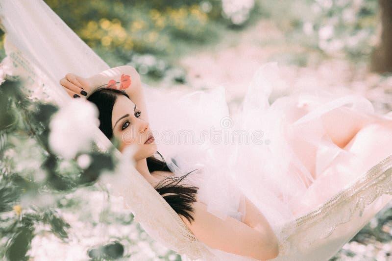 Retrato da morena nova no jardim florescido no th foto de stock royalty free