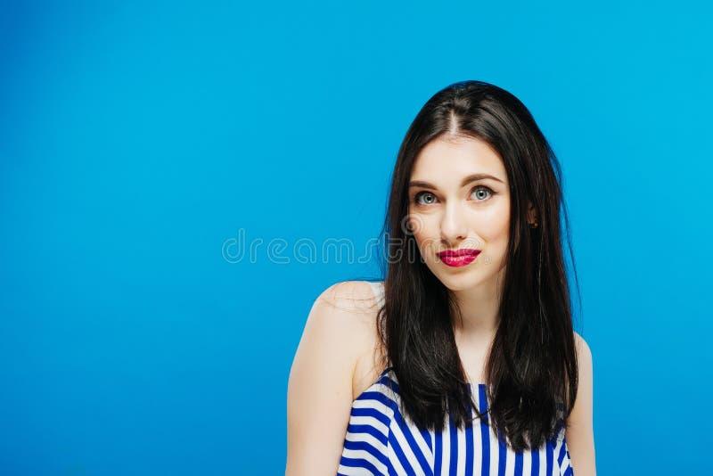 Retrato da morena surpreendida engraçada com o cabelo escuro longo que levanta no estúdio no fundo azul fotos de stock royalty free