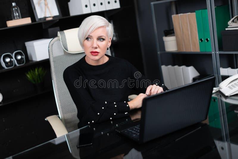 Retrato da mulher à moda que trabalha com o portátil no escritório imagens de stock