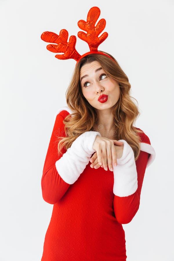 Retrato da mulher adorável 20s que veste as orelhas vermelhas do traje e dos cervos de Santa Claus que sorriem e que estão, isola fotografia de stock royalty free