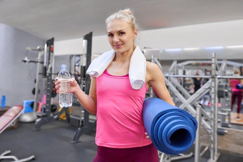 Retrato da mulher adulta de sorriso com a garrafa da água e da esteira dos esportes no health club Conceito do esporte da aptidão foto de stock royalty free