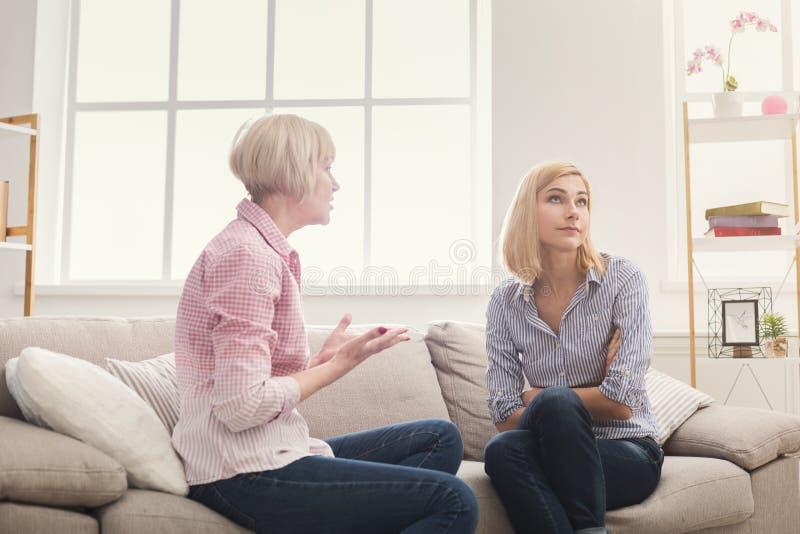 Retrato da mulher adulta e da filha irritadas em casa imagens de stock