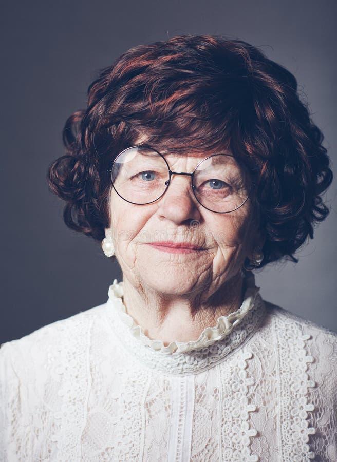Retrato da mulher adulta envelhecida bonita nos vidros, 80 anos velhos imagens de stock