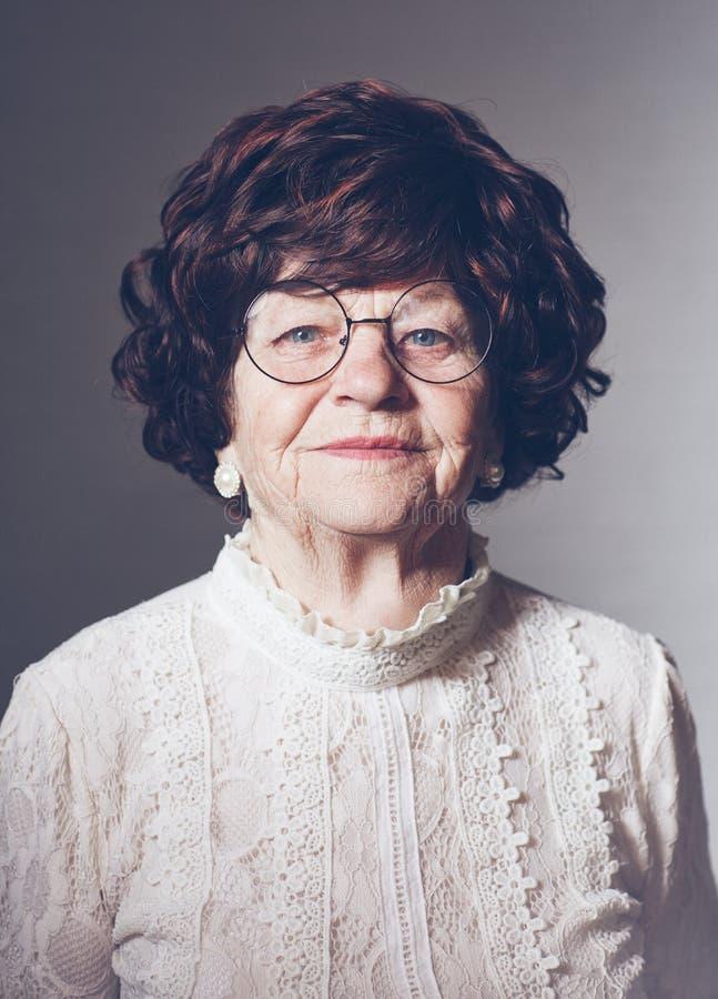 Retrato da mulher adulta envelhecida bonita nos vidros, 80 anos velhos fotografia de stock royalty free