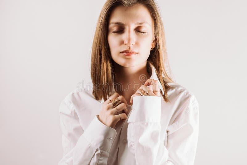 Retrato da mulher adulta nova com o colar guardando fechado dos olhos da camisa branca com suas mãos imagem de stock