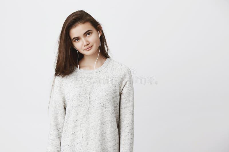 Retrato da mulher adulta nova macia bonita, estando em linha reta sobre o fundo branco ao sorrir e ao vestir foto de stock royalty free