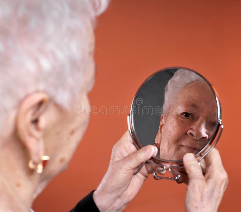 Retrato da mulher adulta que olha em um espelho fotos de stock royalty free