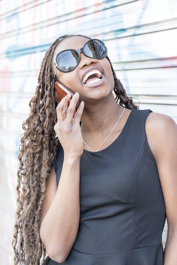 Retrato da mulher africana bonita com óculos de sol que fala por c imagens de stock