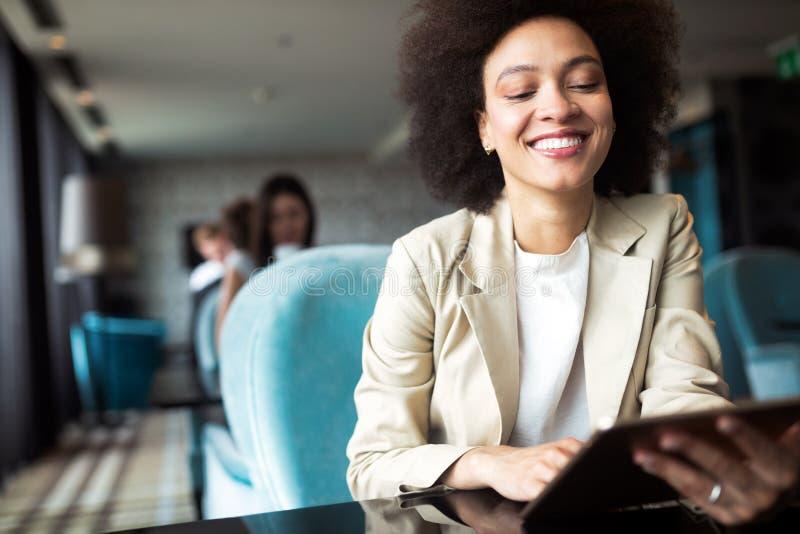 Retrato da mulher africana feliz nova que usa a tabuleta de Digitas fotos de stock royalty free