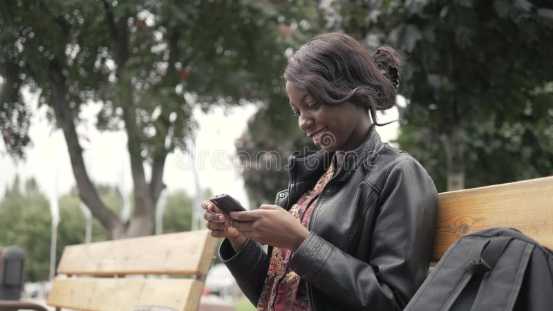 Retrato da mulher africana nova bonita que sorri ao sentar-se fora em um banco que guarda o telefone celular após a universidade fotos de stock