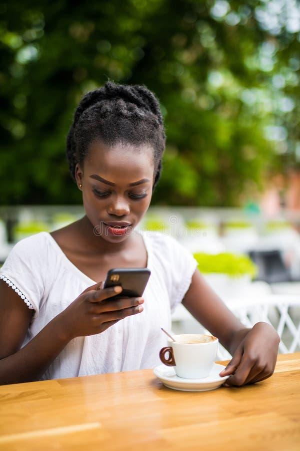 Retrato da mulher africana que usa o telefone celular em um café exterior com portátil e xícara de café na tabela fotos de stock