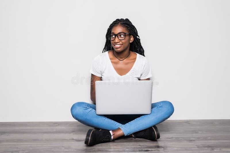 Retrato da mulher afro-americana no assento ocasional no assoalho na pose dos lótus e no portátil guardar isolado sobre o fundo b foto de stock royalty free