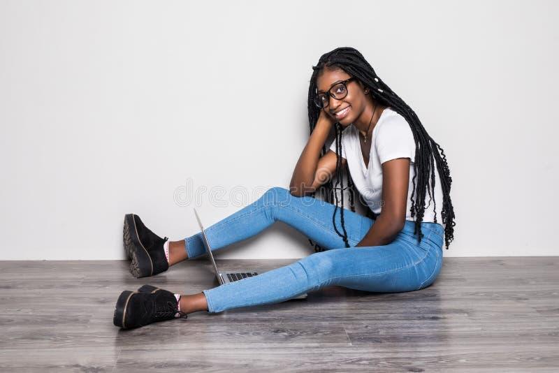 Retrato da mulher afro-americana nova alegre que descansa ao sentar-se em um assoalho sobre o fundo branco imagem de stock