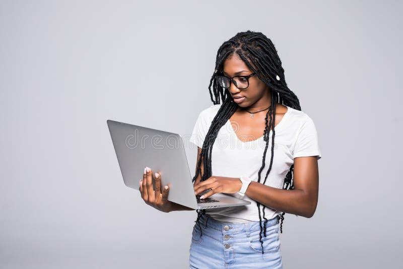 Retrato da mulher afro-americana nova feliz que usa o laptop isolado sobre o fundo branco fotos de stock