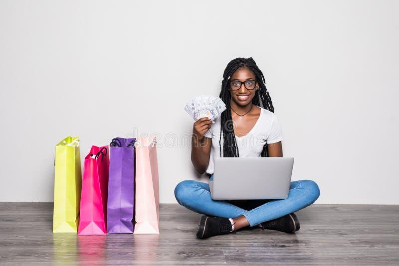 Retrato da mulher afro-americana nova que usa o portátil ao sentar-se em um assoalho com as cédulas dos dólares perto dos sacos d imagens de stock