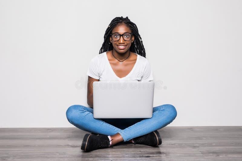 Retrato da mulher afro-americana nova que usa o portátil ao sentar-se em um assoalho com os pés cruzados sobre o fundo branco foto de stock