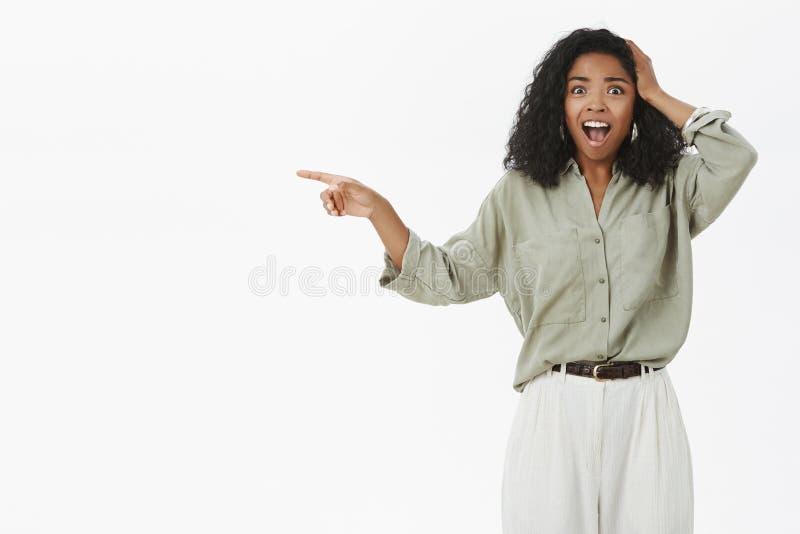 Retrato da mulher afro-americano sem-palavras chocada com o penteado encaracolado que é chocado com acidente terrificando imagem de stock royalty free