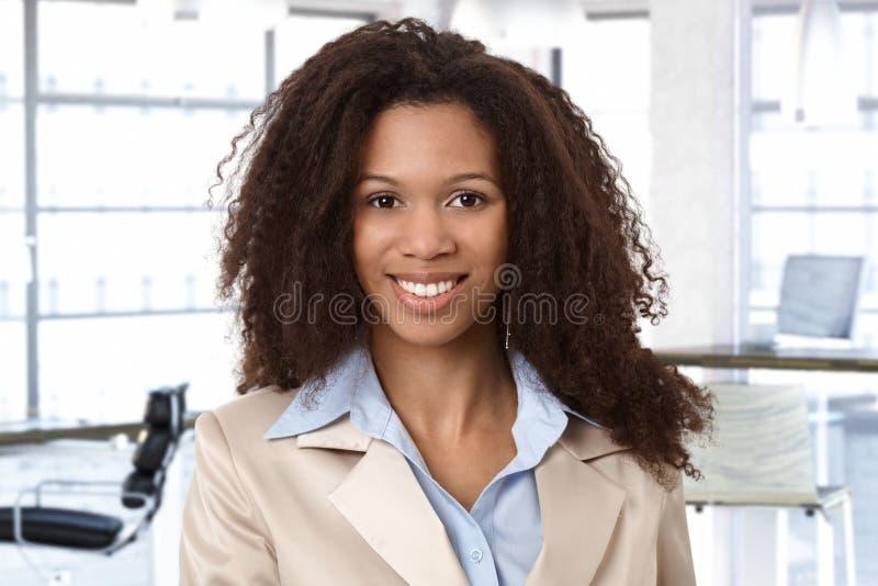 Retrato da mulher afro atrativa no escritório fotos de stock royalty free