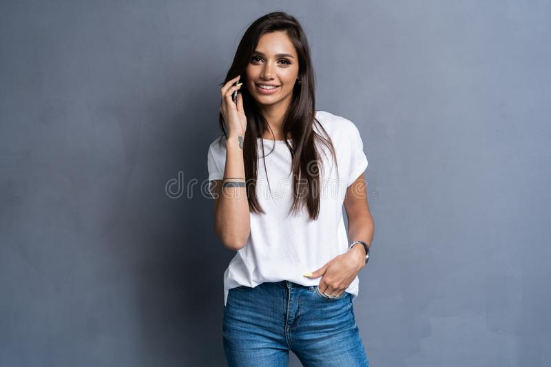 Retrato da mulher alegre bonito que veste o t-shirt básico que fala no telefone celular isolado sobre o fundo cinzento fotografia de stock