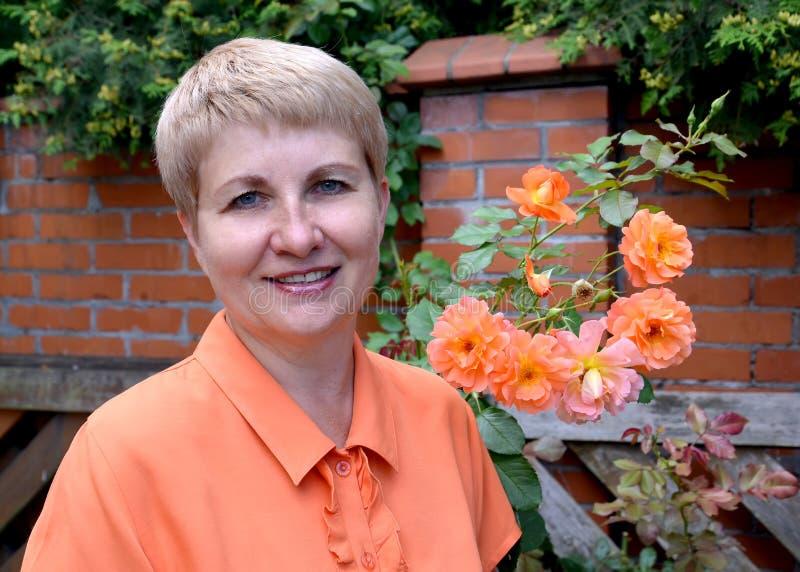 Retrato da mulher alegre dos anos médios com rosas contra uma proteção do tijolo fotos de stock royalty free